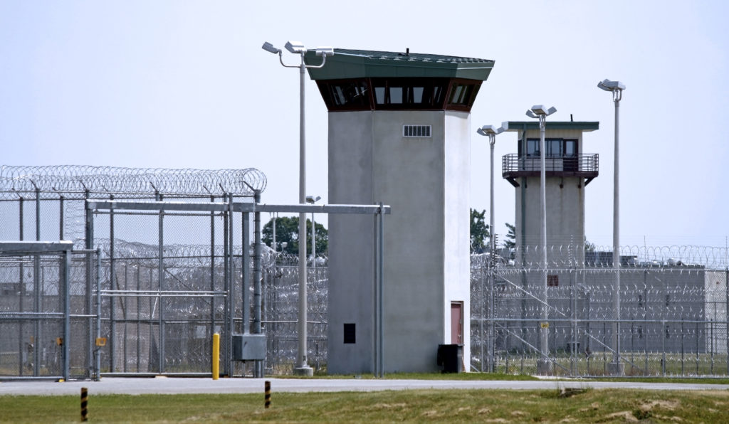 the exterior of a correctional institution with a guard tower and barbed wire fence